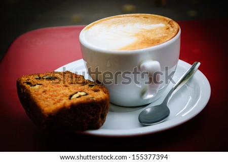 Cup of  cappuccino, slice of carrot pie with walnuts and and glass with brown sugar on the red table in cafe. Outdoor. Selective focus. Shadowed angles.