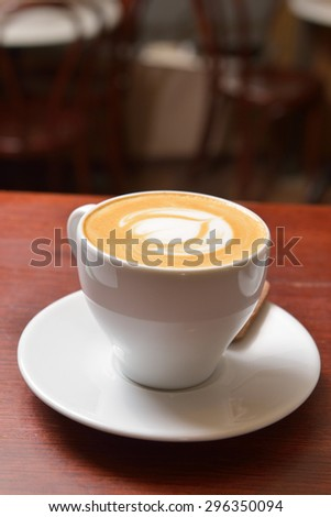 Cup of cappuccino with a pattern on the foam standing - stock photo