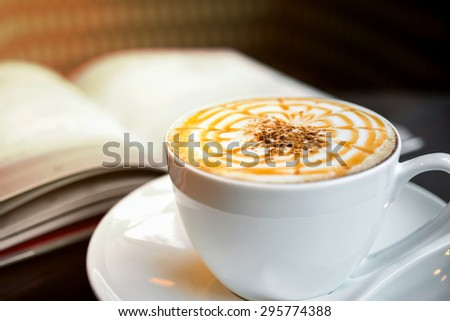 Cup of cappuccino with book in coffee shop  - stock photo