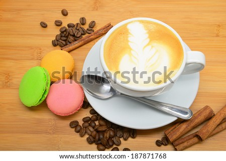 Cup of cappuccino with coffee beans, cookies and cinnamon - stock photo