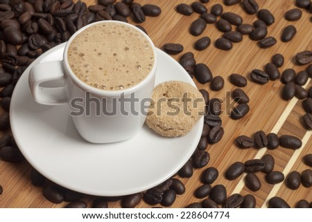 Cup of cappuccino with cookie and spilled out coffee beans.  - stock photo