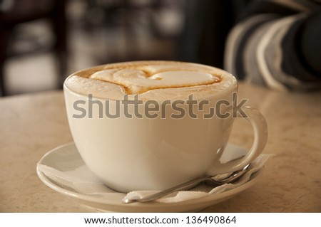 cup of cappuccino with foam and cinnamon hearts - stock photo