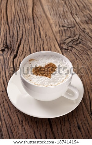 Cup of cappuccino with ground cinnamon in the form of heart on old wooden table. Top view.