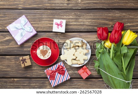 Cup of cappuccino with heart shape and cookies on wooden background.