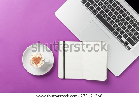 Cup of cappuccino with heart shape and laptop with note on violet background. - stock photo