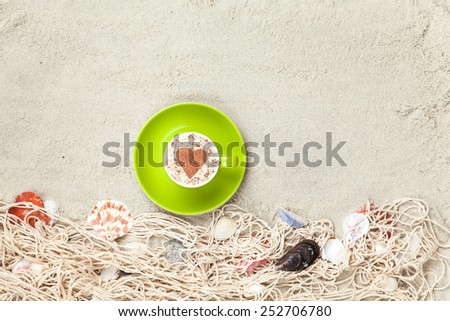 Cup of Cappuccino with heart shape symbol and net with shells on sand