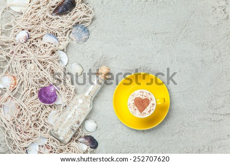 Cup of Cappuccino with heart shape symbol, bottle and net with shells on sand - stock photo