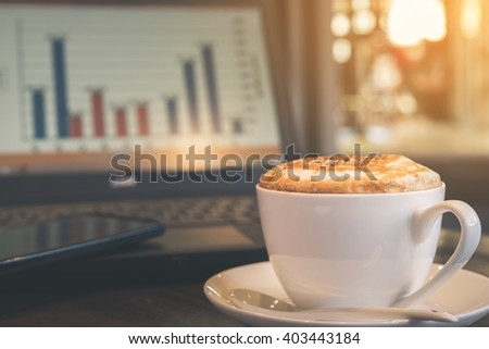 Cup of cappuccino with laptop in coffee shop background, vintage tone