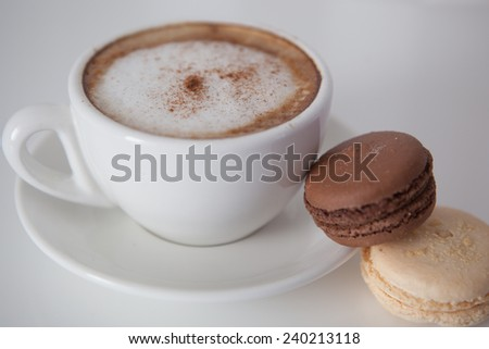 Cup of cappuccino with macaroon cookies and orchid flower on the white table