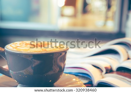 Cup of cappuccino with magazine on blur coffee shop background, vintage tone  - stock photo