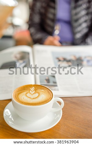 Cup of cappuccino with newspaper on the table - stock photo
