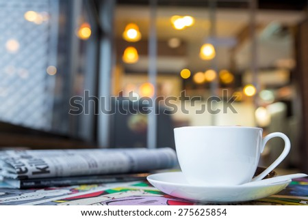 Cup of cappuccino with newspaper on the table, blur coffee shop background - stock photo