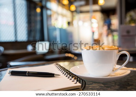 cup of cappuccino with notebook and pen, blur coffee shop background - stock photo