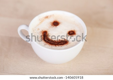 cup of cappuccino with smiley face on millk foam - stock photo