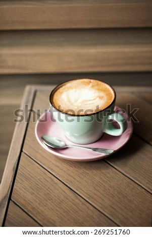 Cup of cappucino on wooden table with graphic lines - stock photo