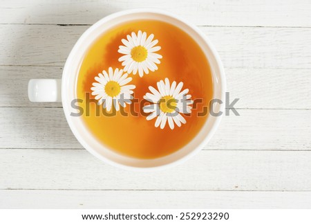 cup of chamomile tea on white wooden table - stock photo