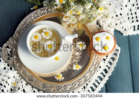 Cup of chamomile tea with chamomile flowers and tasty muffins on tray, on color wooden background - stock photo