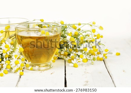 cup of chamomile tea with chamomile flowers on white wooden planks - stock photo