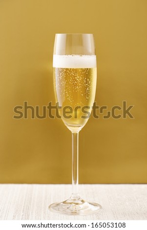 Cup of champagne on golden background sparkling wine - stock photo