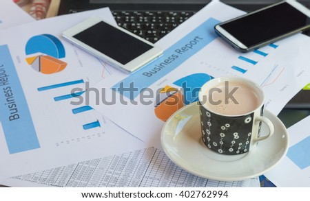Cup of chocolate ,Printed Business Annual Report in Charts and smartphone .business concept. - stock photo
