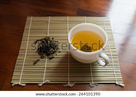 Cup of clear yellow tea and dried tea leaves on a small bamboo mat. - stock photo