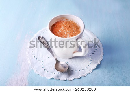 Cup of cocoa with spoon on napkin on wooden background - stock photo