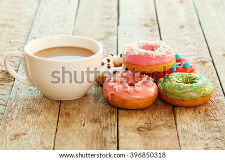 Cup of coffe and colorful donuts on the table - stock photo