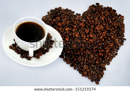 Cup of coffe and heart of beans - stock photo