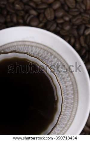 cup of coffee against beans background closeup - stock photo