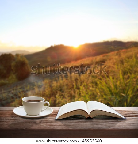 Cup of coffee and a book on a wooden table - stock photo