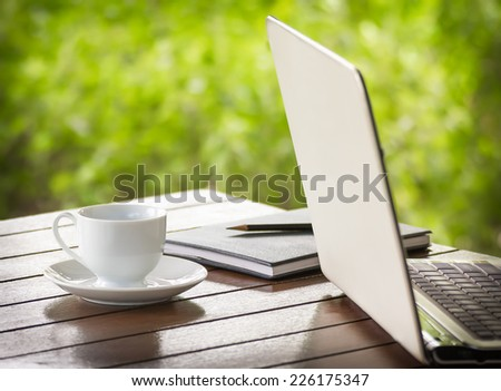 Cup of coffee and a laptop on dark wooden desk