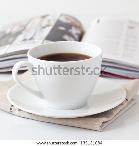 Cup of coffee and a magazine - stock photo