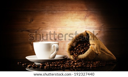 cup of coffee and bag in front of wooden background