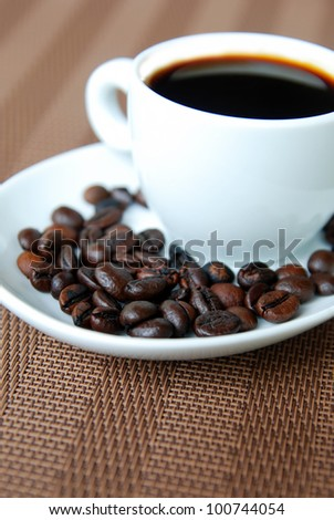 cup of coffee and beans on the side plate