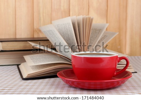 Cup of coffee and books on tablecloth on wooden background - stock photo