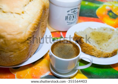 Cup of coffee and bread slice with honey on the table together with loaf of bread and honey ceramic jar. Healthy breakfast with coffee, bread and honey.