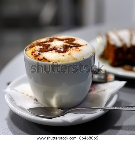 Cup of coffee and cake in cafe, shallow DOF - stock photo