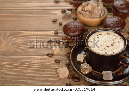 Cup of coffee and chocolate muffins on a brown background - stock photo