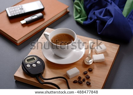 cup of coffee and chronograph on wooden tray