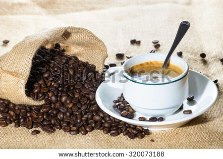 Cup of coffee and coffee beans in sack - stock photo