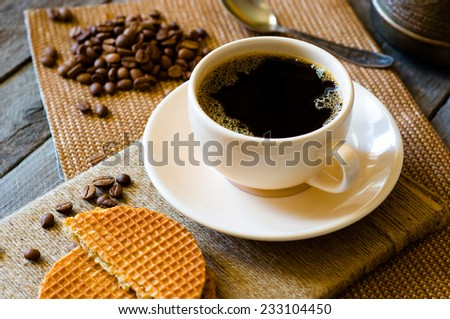 cup of coffee and coffee beans on the table - stock photo