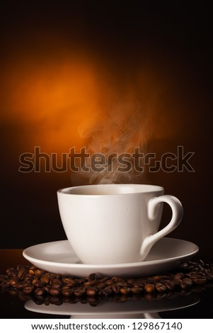 cup of coffee and coffee beans over dark background - stock photo