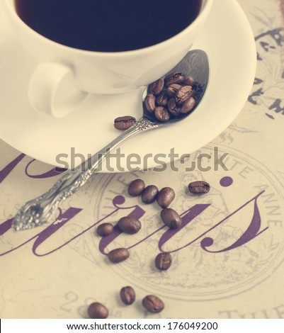 Cup of coffee and coffee beans. Selective focus on coffee beans in spoon - stock photo