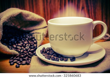 Cup of coffee and coffee beans with smoke on old wooden vintage.