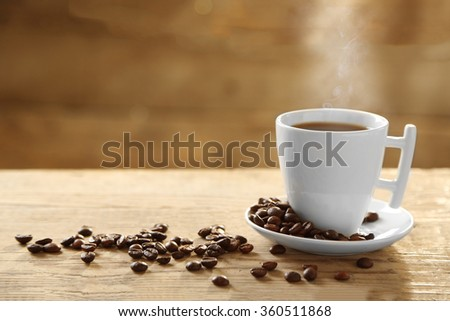 Cup of coffee and coffee grains on wooden background