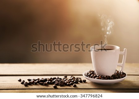 Cup of coffee and coffee grains on wooden table, on gray background - stock photo