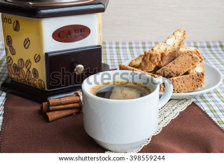 Cup of coffee and coffee mill on a light background with cinnamon and cookies - stock photo