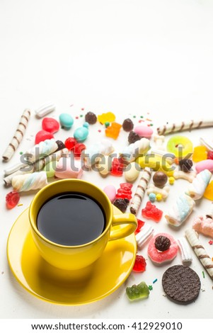 Cup of coffee and colorful candies on white background - stock photo