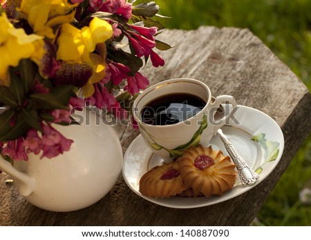 cup of coffee and cookies in the garden outdoors - stock photo