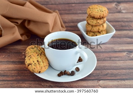 Cup of coffee and cookies on wooden background